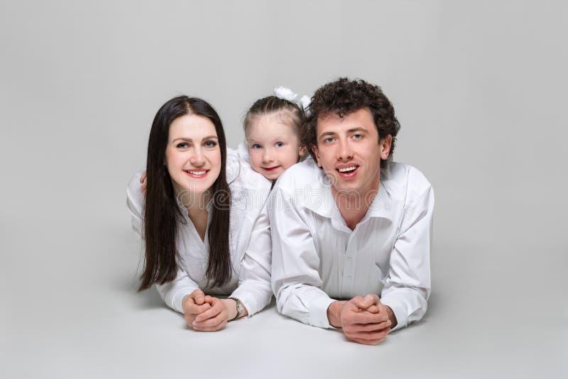 Portret van een gelukkige familie De ouders leunen op ellebogen en hun dochter die hen koesteren Op witte achtergrond stock foto