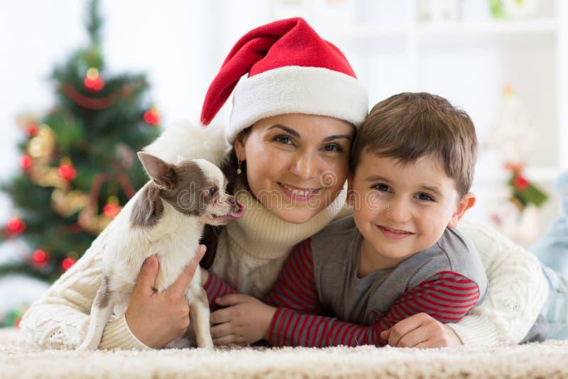 Portret van een gelukkige familie en de hond die samen Kerstmistijd doorbrengen thuis dichtbij de Kerstmisboom stock fotografie