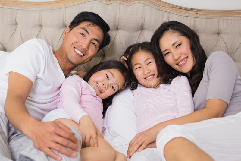Portret van een gelukkige familie van vier die in bed liggen stock foto