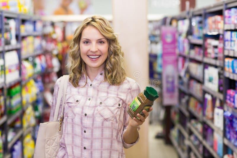 Portret van een gelukkige glimlachende blondevrouw die een product in haar handen hebben stock fotografie