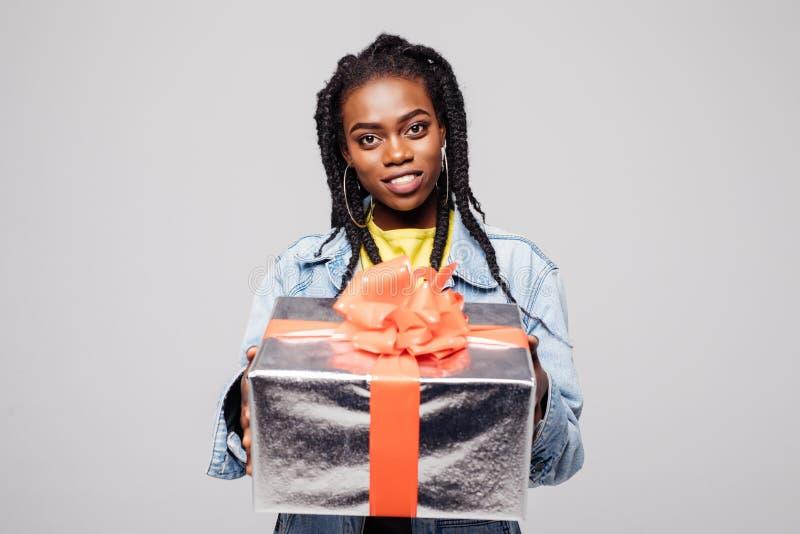Portret van een gelukkige jonge afro Amerikaanse vrouw die huidige die doos houden over grijze achtergrond wordt geïsoleerd royalty-vrije stock foto's