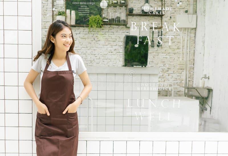 Portret van een gelukkige jonge Aziatische barista in schort die en weg voor haar kleine koffiewinkel omhoog glimlachen kijken, t royalty-vrije stock fotografie