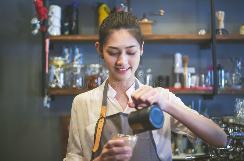 Portret van een gelukkige jonge Aziatische barista in schort het glimlachen voorbereidingen treffende en gietende melk in hete ko royalty-vrije stock afbeelding