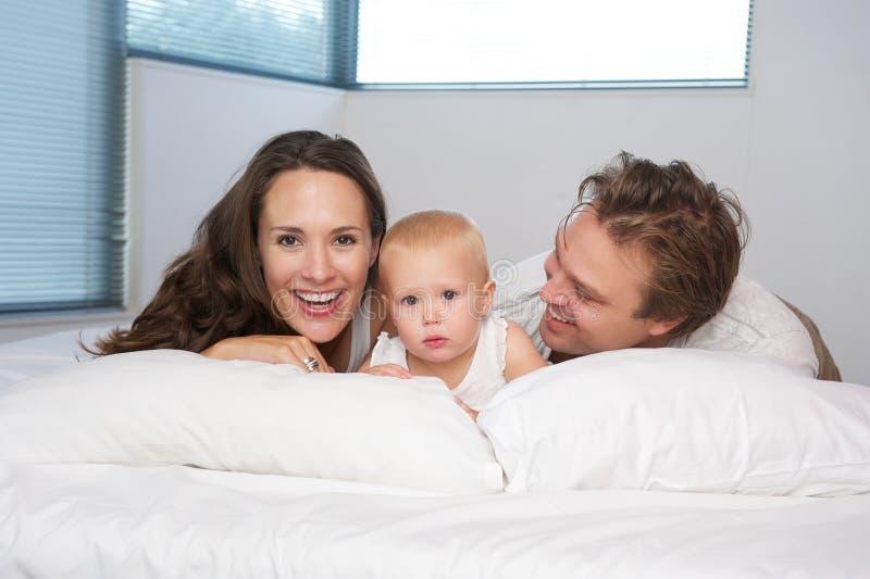 Portret van een gelukkige jonge familie die in bed met leuke baby liggen royalty-vrije stock afbeeldingen