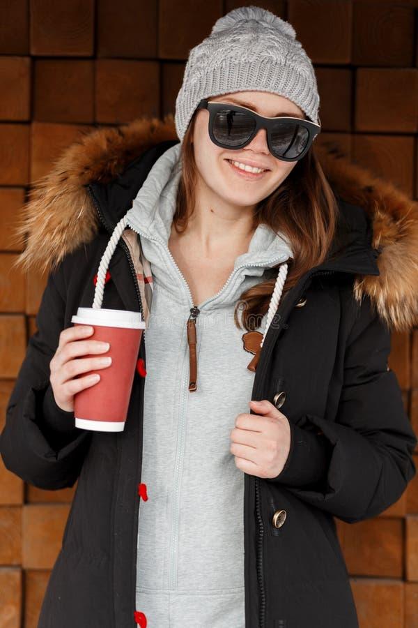 Portret van een gelukkige jonge hipstervrouw in zonnebril in gebreide hoed in een de winter modieus jasje met een bontkap met een stock afbeelding