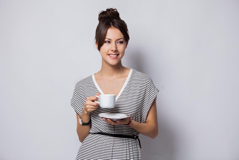 Portret van een gelukkige jonge kop van de bedrijfsdievrouwenholding van koffie over witte achtergrond wordt geïsoleerd stock fotografie