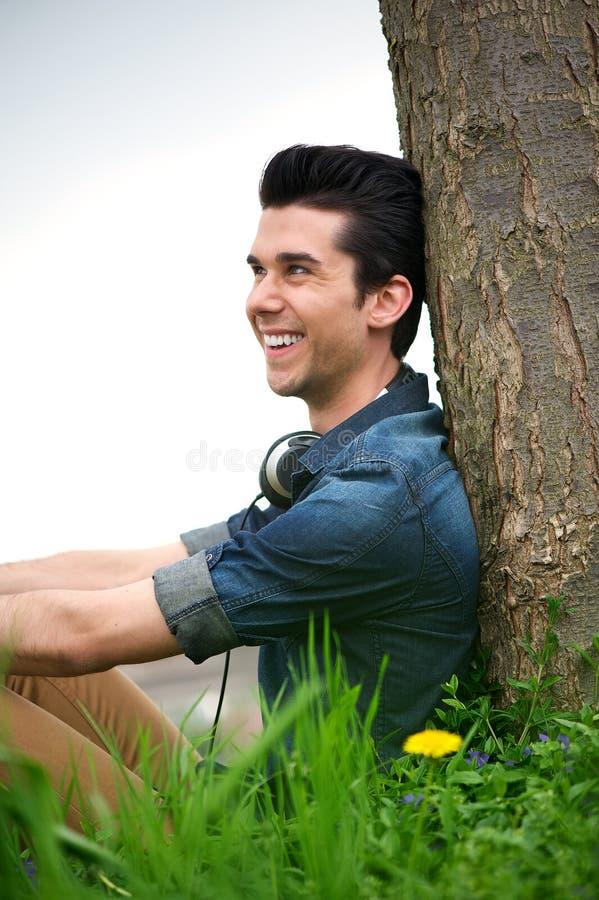 Portret van een gelukkige jonge mens die tegen een boom in openlucht ontspannen stock afbeelding