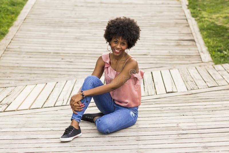 Portret van een Gelukkige jonge mooie zitting van de afro Amerikaanse vrouw stock afbeeldingen