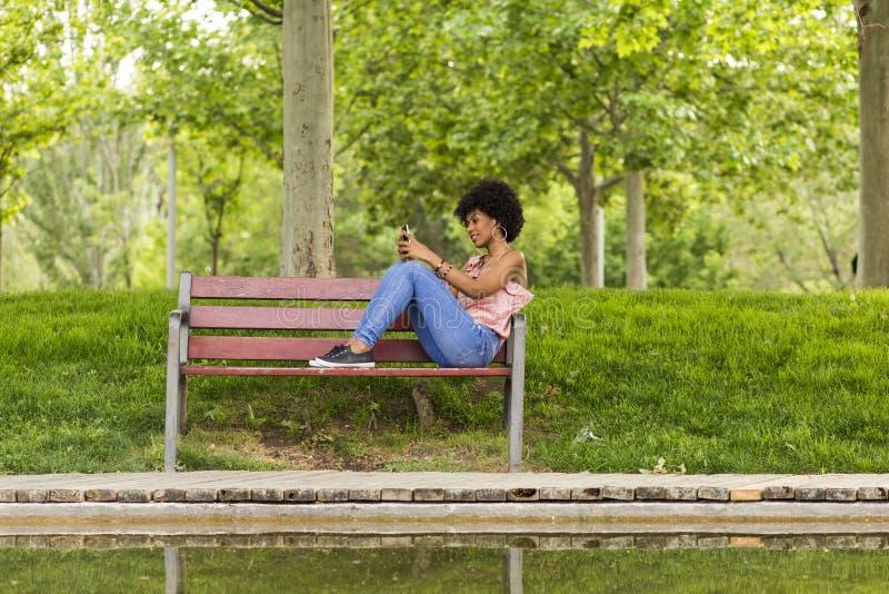 Portret van een Gelukkige jonge mooie zitting van de afro Amerikaanse vrouw stock foto
