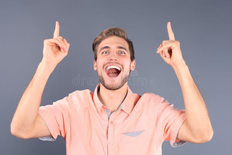 Portret van een gelukkige jonge toevallige mens die op exemplaarruimte benadrukken die over grijze achtergrond wordt geïsoleerd stock afbeeldingen