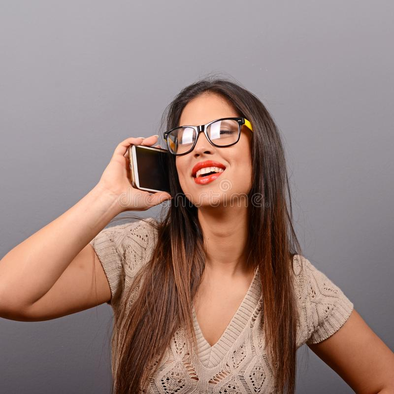 Portret van een gelukkige jonge vrouw die op een cellphone tegen grijze achtergrond spreken royalty-vrije stock afbeeldingen