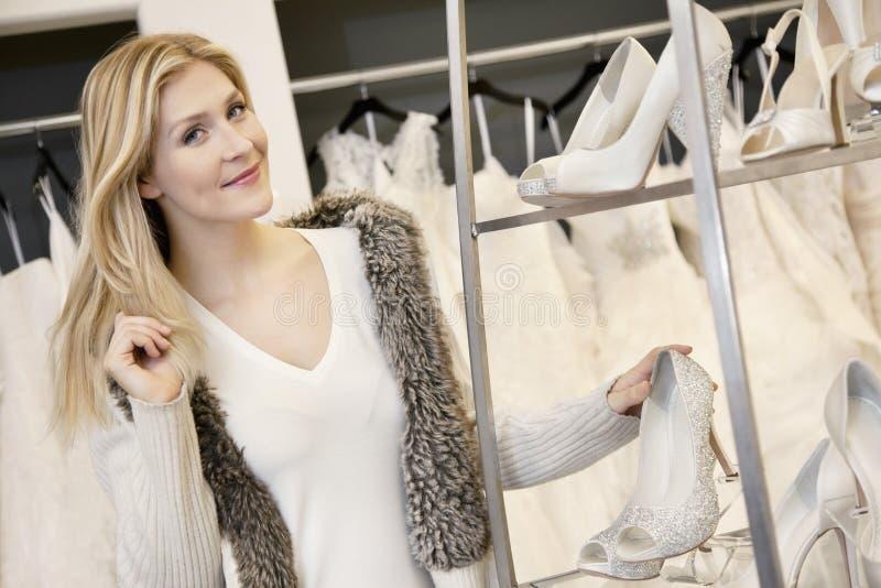 Portret van een gelukkige jonge vrouw die zich door schoeiseltribune bevindt in bruids boutique stock afbeelding