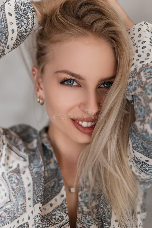 Portret van een gelukkige jonge vrouw met een mooie glimlach met blauwe ogen met sexy lippen met blond haar in een modieus overhe royalty-vrije stock fotografie