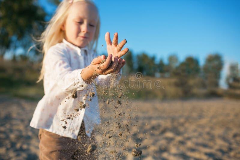 Portret van een gelukkige kleine dochterspelen met een zand op een strand stock afbeelding