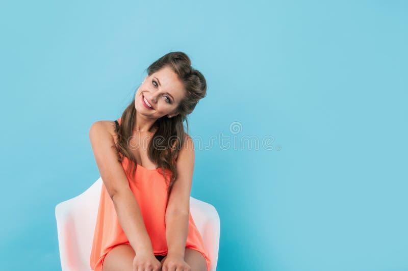 Portret van een gelukkige leuke vrouwenzitting op de stoel stock afbeeldingen