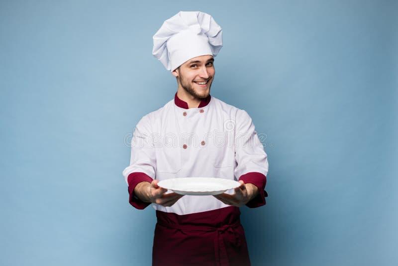 Portret van een gelukkige mannelijke chef-kokkok die zich met plaat bevinden die op lichtblauwe achtergrond wordt geïsoleerd stock afbeelding