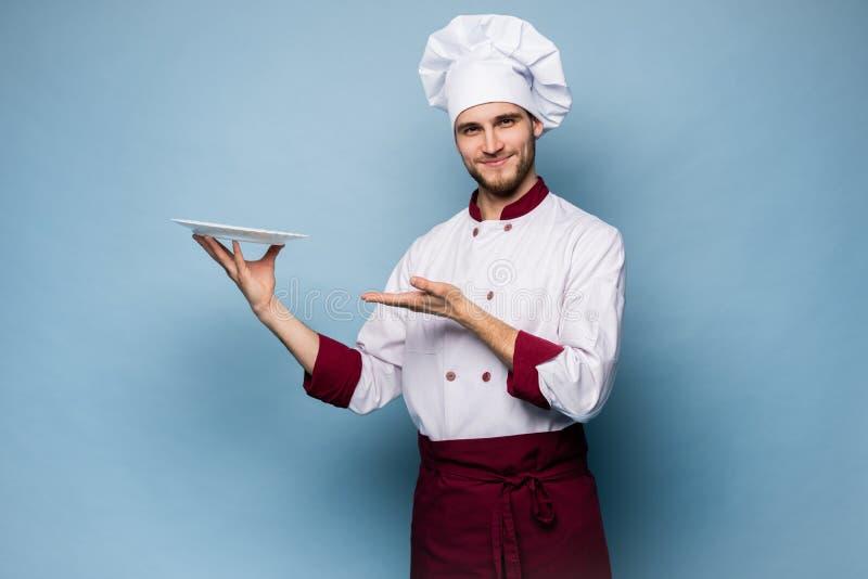 Portret van een gelukkige mannelijke chef-kokkok die zich met die plaat bevinden op lichtblauwe achtergrond wordt geïsoleerd royalty-vrije stock foto's