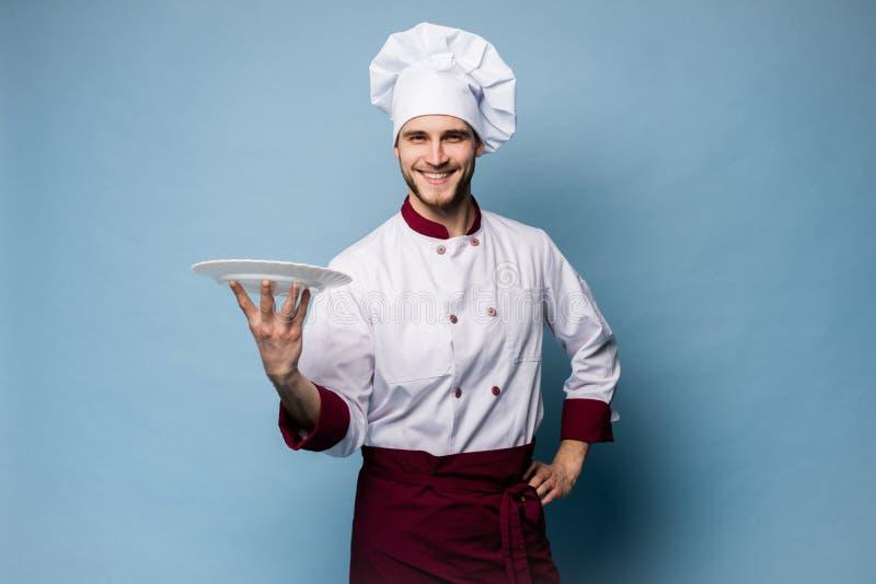Portret van een gelukkige mannelijke chef-kokkok die zich met die plaat bevinden op lichtblauwe achtergrond wordt geïsoleerd stock afbeeldingen