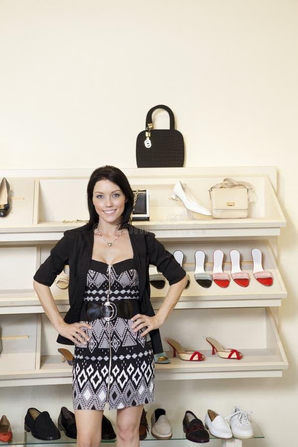Portret van een gelukkige medio volwassen vrouw die zich met handen op heupen in schoeiselopslag bevinden royalty-vrije stock foto