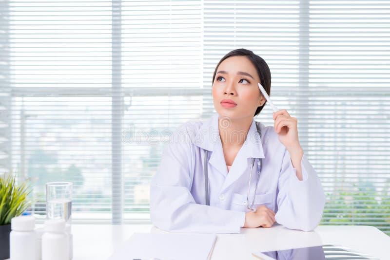 Portret van een gelukkige nadenkende vrouwelijke arts stock fotografie