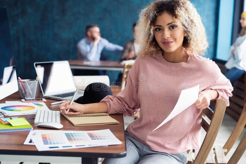 Portret van een gelukkige toevallige onderneemsterzitting bij haar werkplaats in bureau stock afbeeldingen
