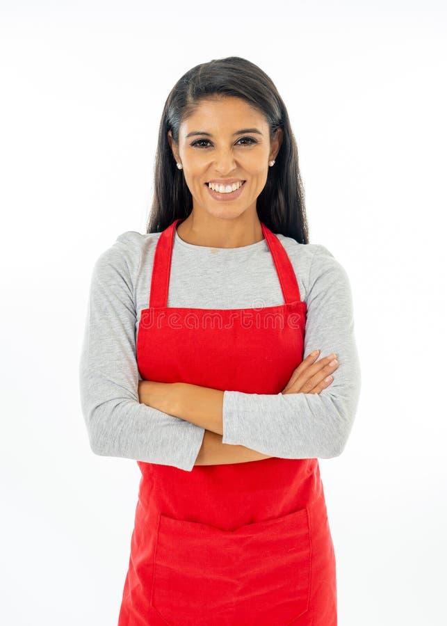 Portret van een gelukkige trotse mooie Latijnse vrouw die een rode schort dragen die het maken van duim op gebaar leren te koken  royalty-vrije stock foto's