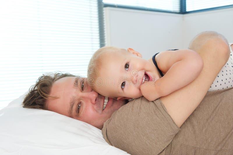 Portret van een gelukkige vader die in bed liggen en leuke baby koesteren stock fotografie
