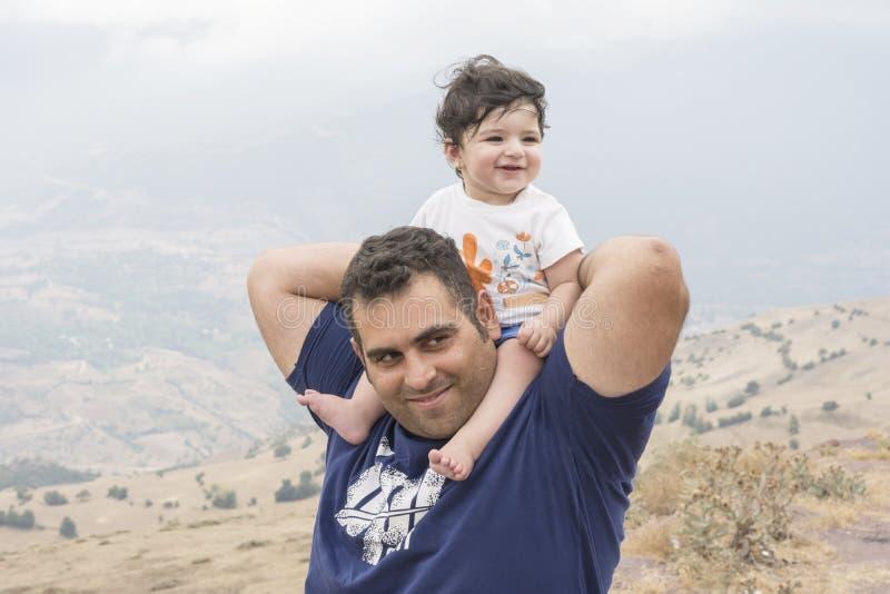 Portret van een gelukkige vader die haar meisje op schouder vervoeren royalty-vrije stock foto