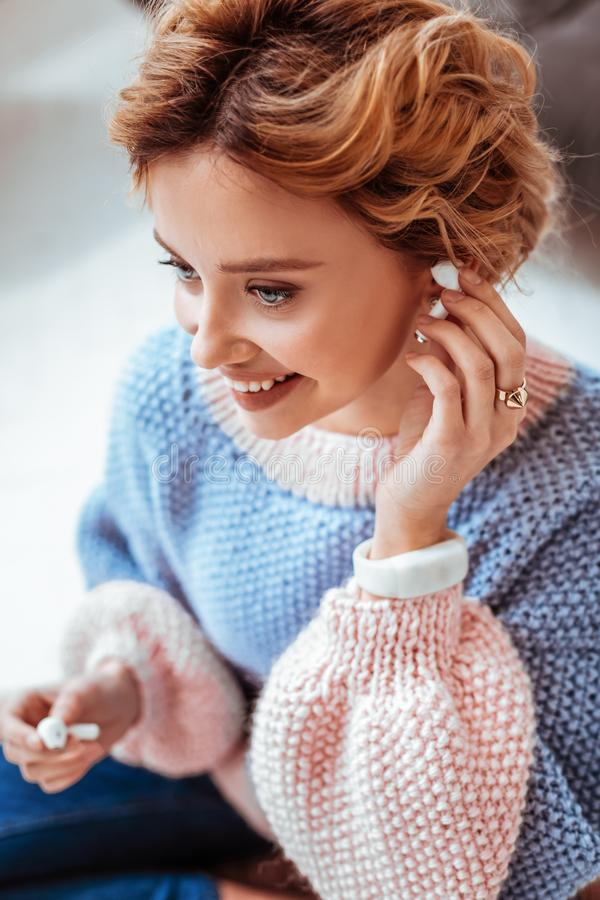 Portret van een gelukkige vrolijke vrouw die aan muziek luisteren stock afbeelding