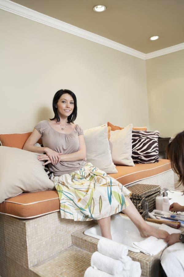 Portret van een gelukkige vrouw die pedicure in beauty spa krijgen royalty-vrije stock afbeelding