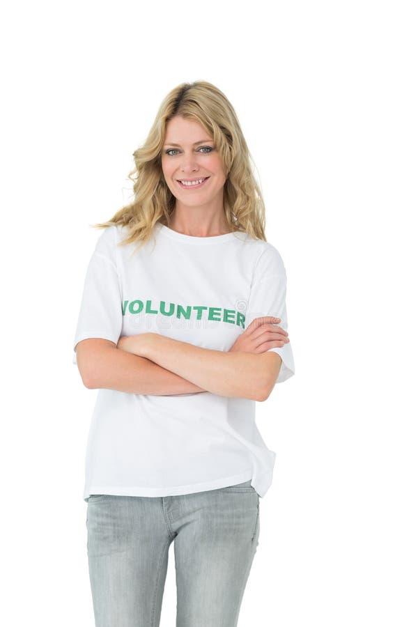 Portret van een gelukkige vrouwelijke vrijwilliger met gekruiste wapens stock foto