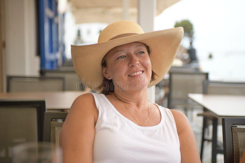 Portret van een gelukkige vrouwenzitting naast het overzees en dagdromen royalty-vrije stock afbeelding