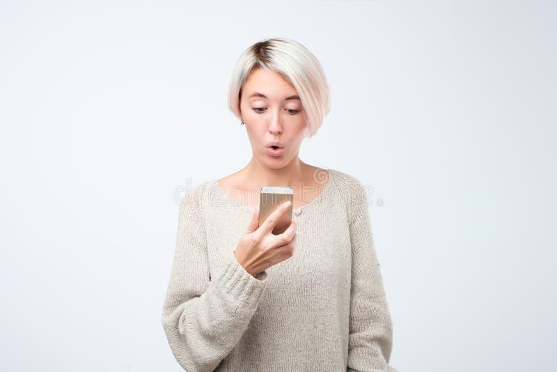 Portret van een geschokt jong meisje die het mobiele telefoonscherm bekijken in verrassingslezing sms stock afbeelding