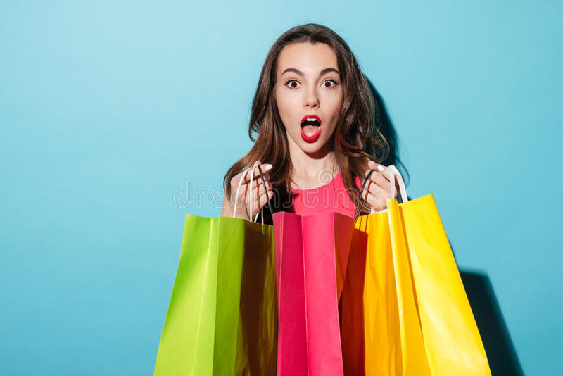 Portret van een geschokt mooi meisje die kleurrijke het winkelen zakken houden royalty-vrije stock afbeelding