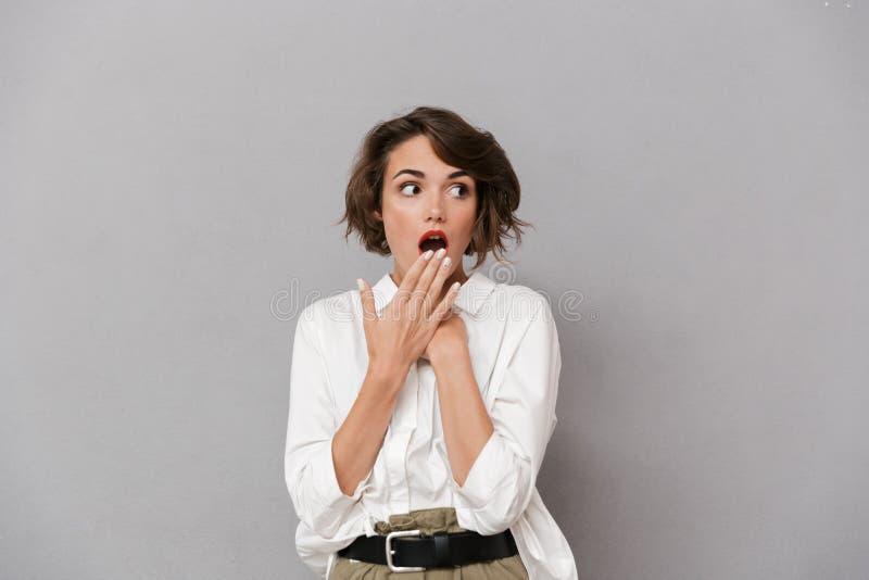 Portret van een geschokte jonge vrouw gekleed in wit overhemd stock afbeeldingen