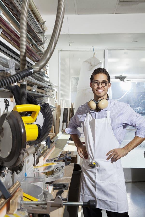 Portret van een geschoolde arbeider die zich met handen op heupen in workshop bevinden stock afbeeldingen