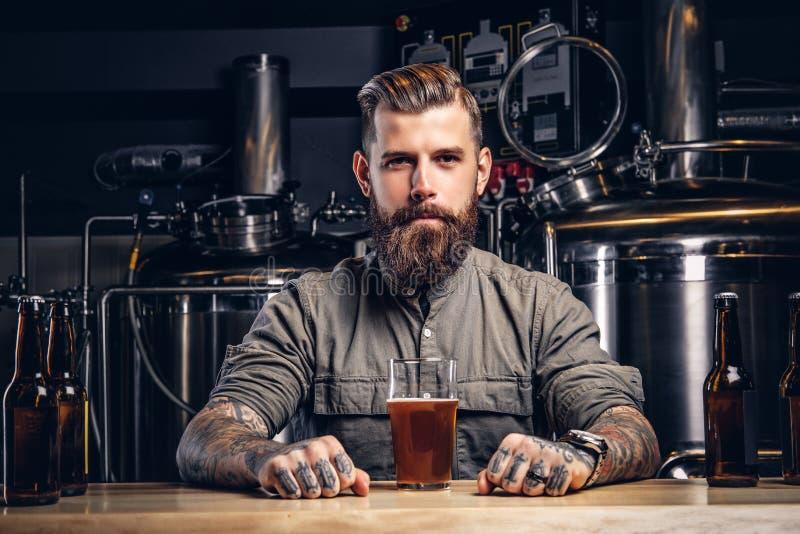 Portret van een getatoeeerd hipster mannetje met modieuze baard en haar in overhemdszitting bij de barteller met glas bier stock fotografie