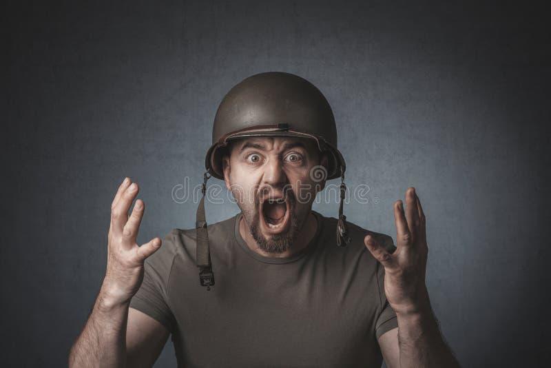 Portret van een gillende militair met open wapens stock fotografie