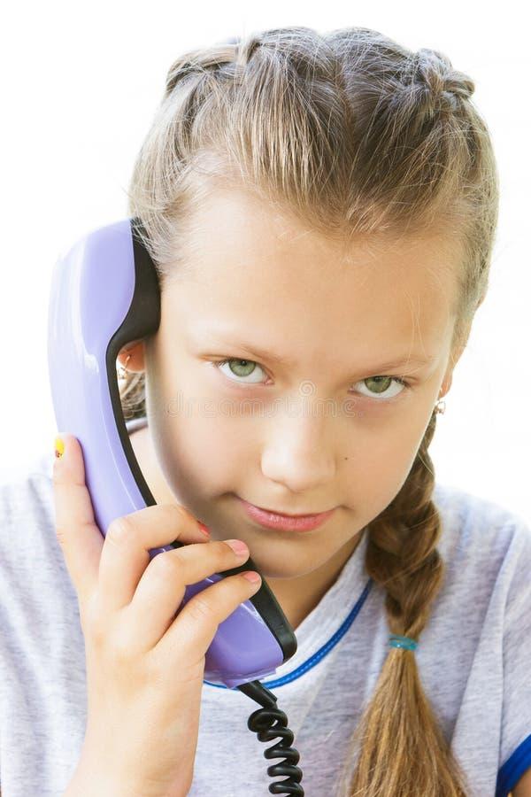 Portret van een girlie met een zaktelefoon van een oude telefoon op een witte achtergrond royalty-vrije stock foto