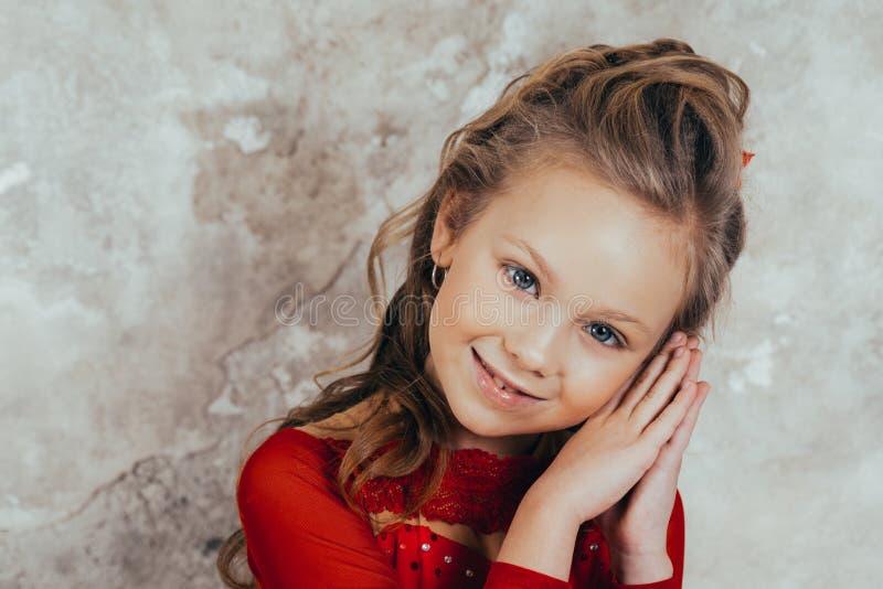 Portret van een glimlachend jong meisje in een rode kleding en met een mooi kapsel Het schot van de studio royalty-vrije stock fotografie