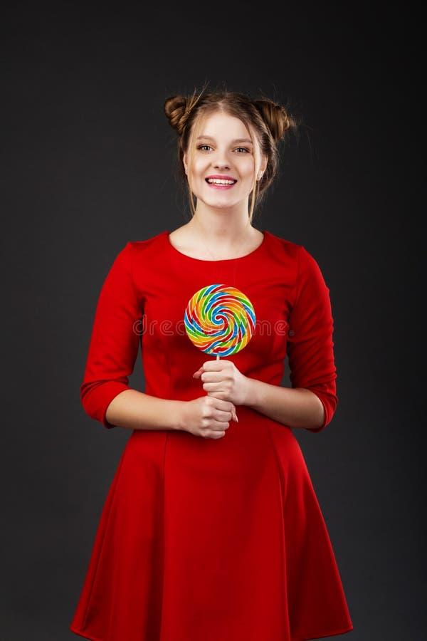 Portret van een glimlachend jong mooi meisje in een rode kleding met a stock foto