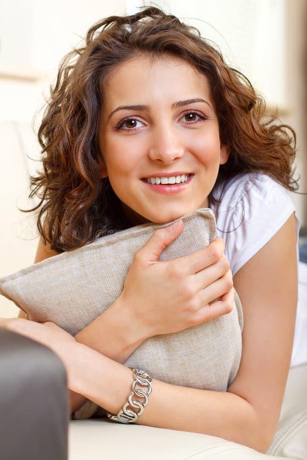Portret van een glimlachend meisje dat een hoofdkussen houdt stock foto's