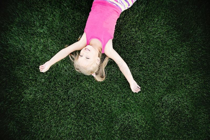 Portret van een glimlachend meisje dat op groen gras ligt royalty-vrije stock foto's