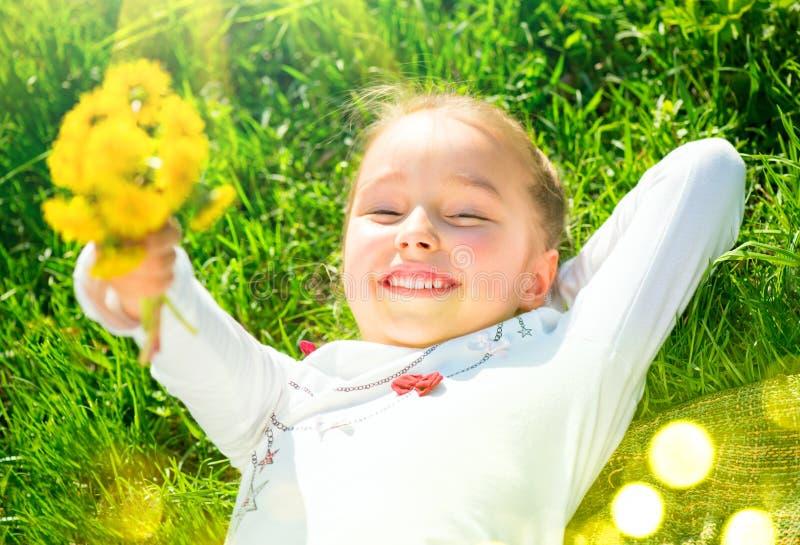 Portret van een glimlachend meisje die op groen gras met een bos van gele paardebloemen liggen Leuke vijf jaar oud kind die natur stock afbeelding