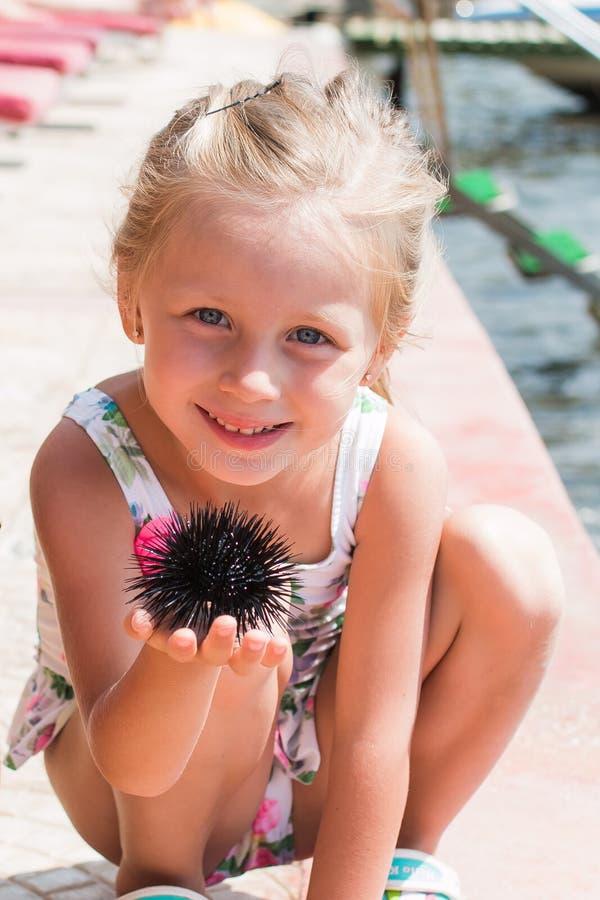 Portret van een glimlachend meisje met zeeëgel in de handen van royalty-vrije stock fotografie