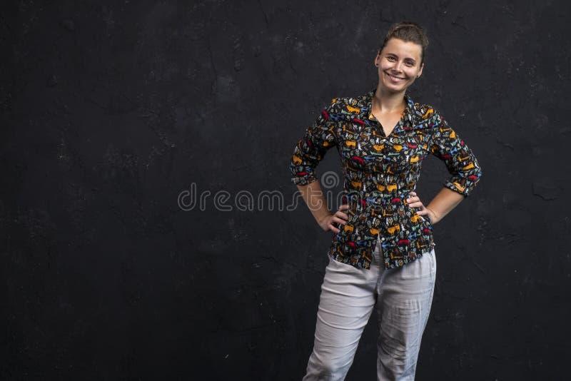 Portret van een glimlachend meisje op een zwarte muurachtergrond Kaukasisch meisje in modieuze de jeugdkleren Het portret van de  royalty-vrije stock foto's