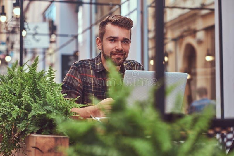 Portret van een glimlachend modieus gebaard mannetje met een modieus kapsel, gekleed in een flaneloverhemd, die in een koffie zit royalty-vrije stock fotografie