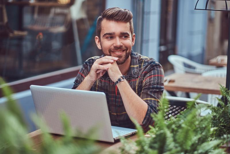 Portret van een glimlachend modieus gebaard mannetje met een modieus kapsel, gekleed in een flaneloverhemd, die in een koffie zit stock afbeeldingen