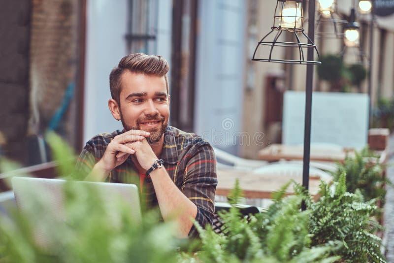 Portret van een glimlachend modieus gebaard mannetje met een modieus kapsel, gekleed in een flaneloverhemd, die in een koffie zit stock foto's