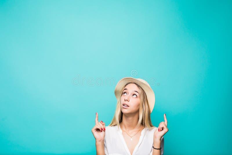Portret van een glimlachend mooi de zomermeisje die in strohoed twee die vingers benadrukken op copyspace over blauwe achtergrond stock foto